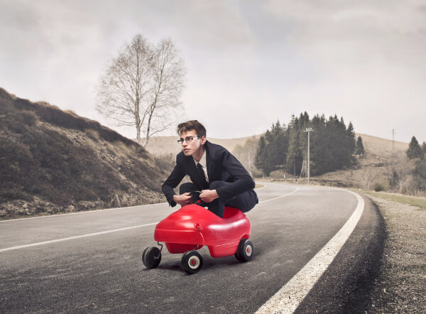 Hypnotised man imaginging he is hunched into a toy childs racing car on an empty road