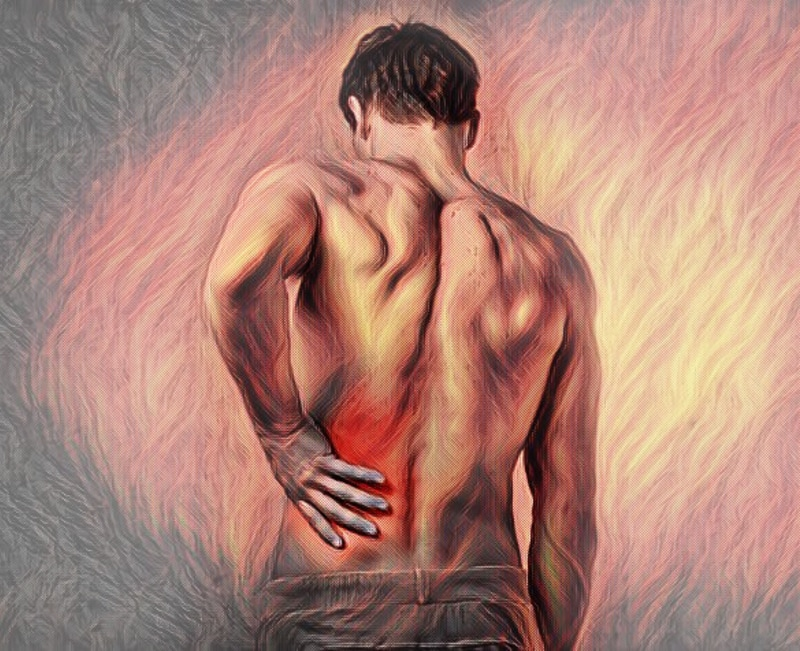 Man holding an inflamed, painful area of his back, requiring hypnotherapy for pain management.