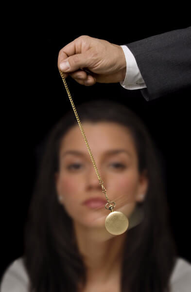 A woman being hypnotised by a swinging pocket watch, her eyes focused on the hypnotic watch itself.