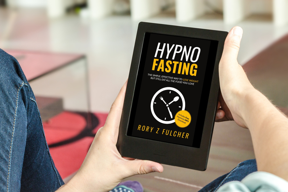 Person holding a tablet showing the cover of Hypno-Fasting, a weightloss book by Rory Z fulcher