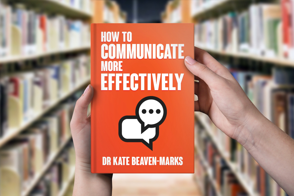 Person in a library looking at a copy of How to Communicate More Effectively by Dr Kate Beaven-Marks, with the book held in front of them
