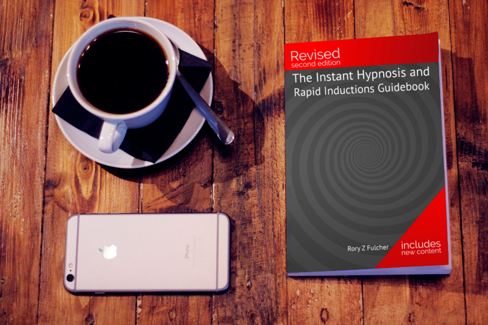 Rory Z Fulcher's book, The Instant Hypnosis and Rapid Inductions Guidebook, on a table with an iphone and a cup of black coffee