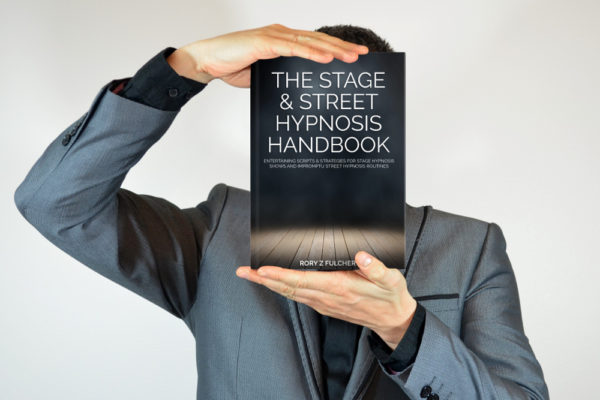 Man in a grey suit holding The Stage & Street Hypnosis Handbook by Rory Z Fulcher in front of his face with both hands
