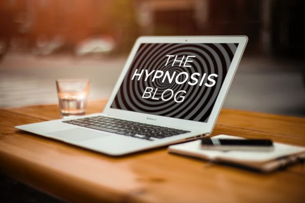 Laptop computer on a clean wooden desk showing the words 'the hypnosis blog' on a spiral background