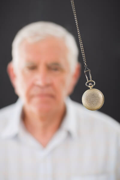 Man being hypnotised during the hypnotherapy process, with a pocket watch being swung before his eyes.