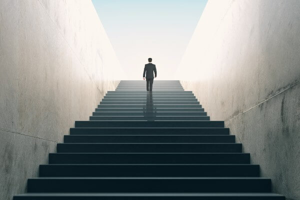 Metaphorical image of a hypnotherapy client walking up a long staircase towards a bright light, which represents their goal success.