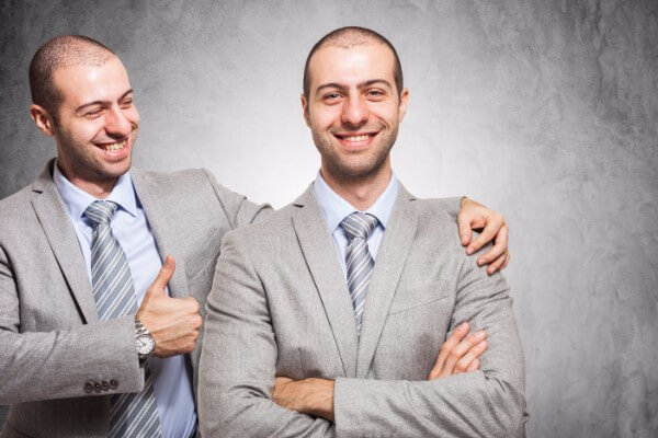 A man having engaged in the ego strengthening portion of the hypnotherapy process stands next to another version of himself, both smiling, the second version of himself is giving him support and putting his thumb up.