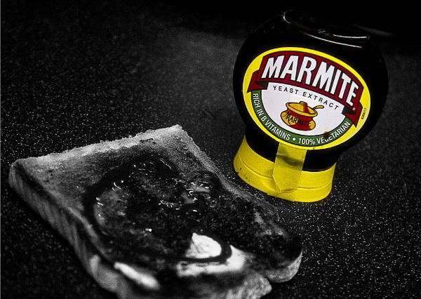 Jar of marmite on a table next to a greyscale piece of toast smothered in dark black marmite