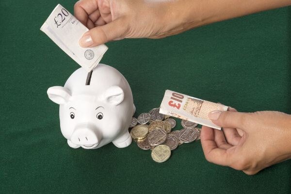 Person saving money for hypnosis training, putting a £20 note into a piggy bank