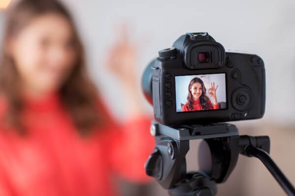 Woman in red shirt in front of a camera, ready to practice her hypnosis skills that she just learned on an online hypnosis course.