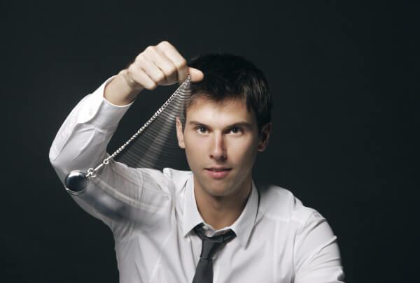 Hypnotist man confidently using a hypnotic pocket watch to hypnotise someone.