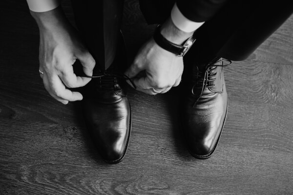 Stage hypnotist bent over tying shoes, getting ready for a business meeting.
