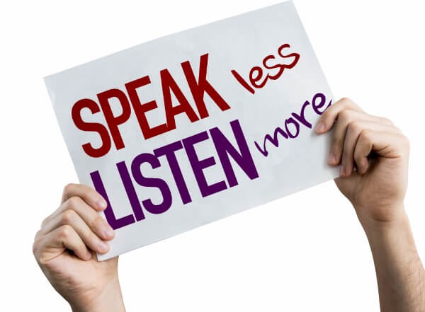 hands holding an active listening sign, reading speak less, listen more.