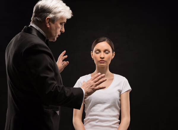 Male hypnotist standing in front of sitting hypnotised girl, giving suggestions to pretend to go into hypnosis.