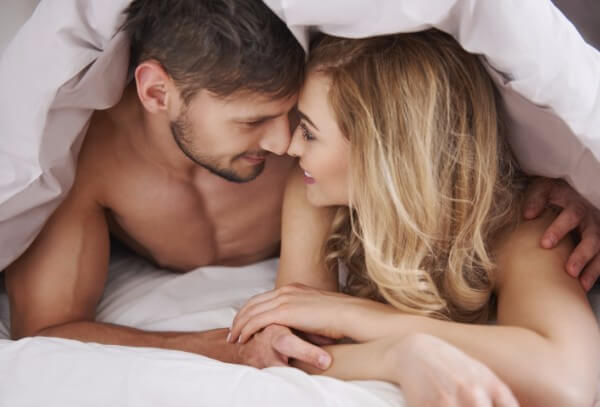 a couple in bed using erotic hypnosis with each other