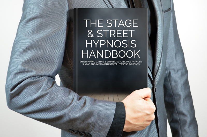 man holding a copy of Rory Z Fulcher's Stage & Street Hypnosis Handbook