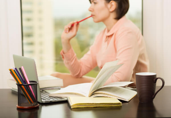 Hypnotherapist sat at desk, planning a stress and anxiety hypnotherapy session, surrounded by hypnotherapy books