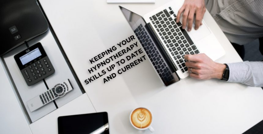 Modern, clean desk with laptop and coffee. Text on desk reads 'keeping your hypnotherapy skills up to date and current'